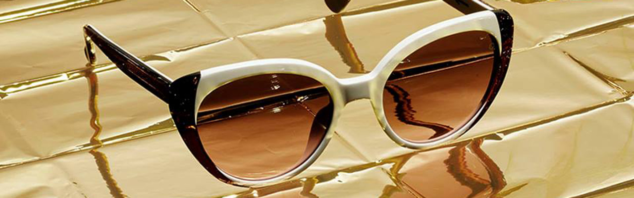 a pair of dark sunglasses on a gold-foil background