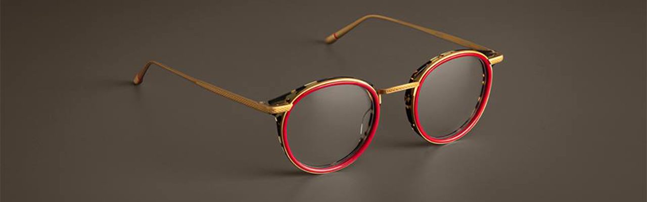 eyeglass frames with red frames and gold colored trim